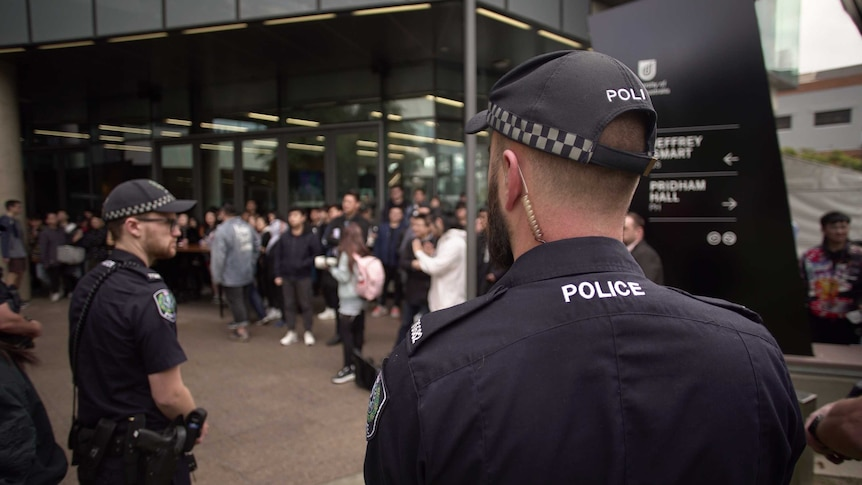 Two police officers stand among hundreds of protesters in front of a university building