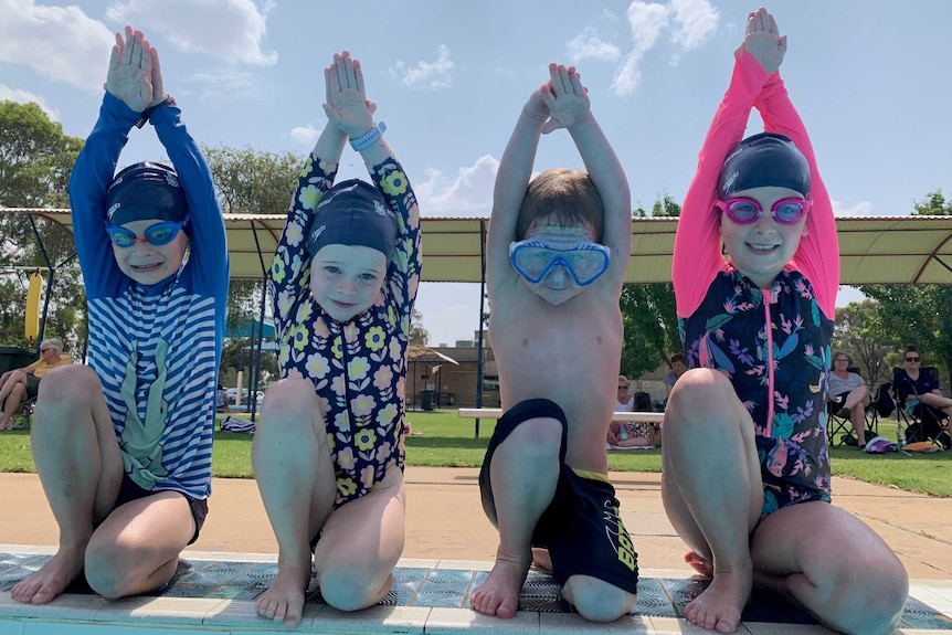 four children with goggles kneel on edge of pool with hands above head ready to dive in.