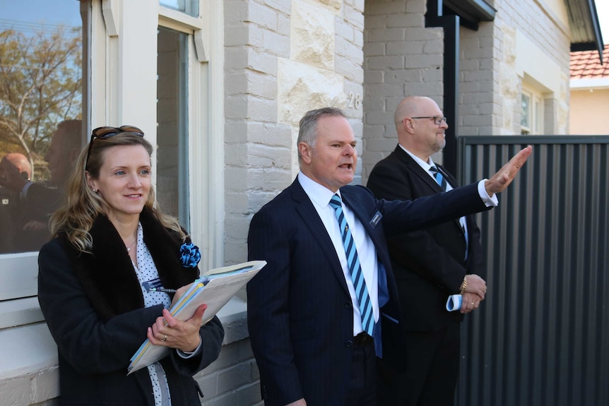 An auctioneer and his helpers auctioning a house auction in Adelaide