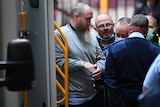 A handcuffed man with a long beard surrounded by guards as he enters court.