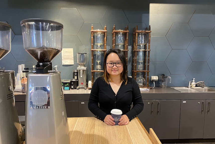 A woman stands in front of the counter at a cafe.