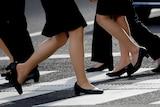 Women in high heels walk at a business district in Tokyo, Japan, June 4, 2019.