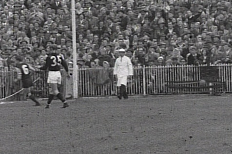 A black and white photo of an umpire at the MCG during the 1957 grand final