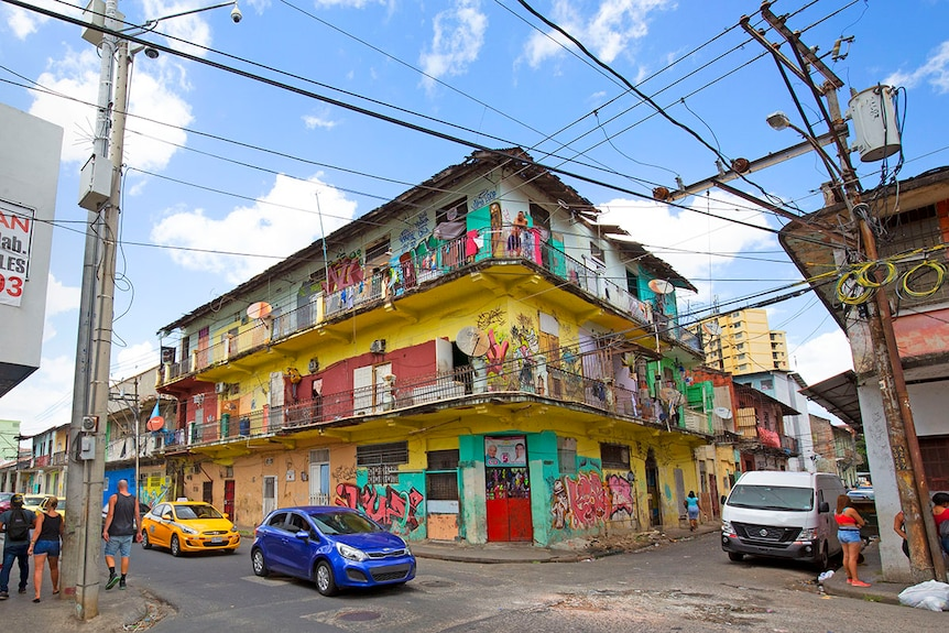 Locals stand out on the balcony of a bright yellow apartment block, watching victor show tourists down the street.