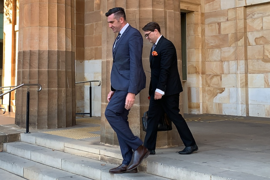 Two men in suits walk down stairs outside a sandstone building