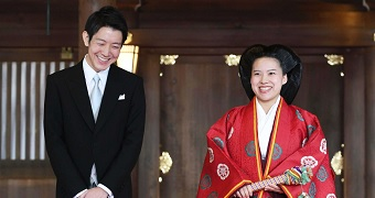 Kei Moriya, left, stands next to Princess Ayako, who is wearing a traditional red dress.