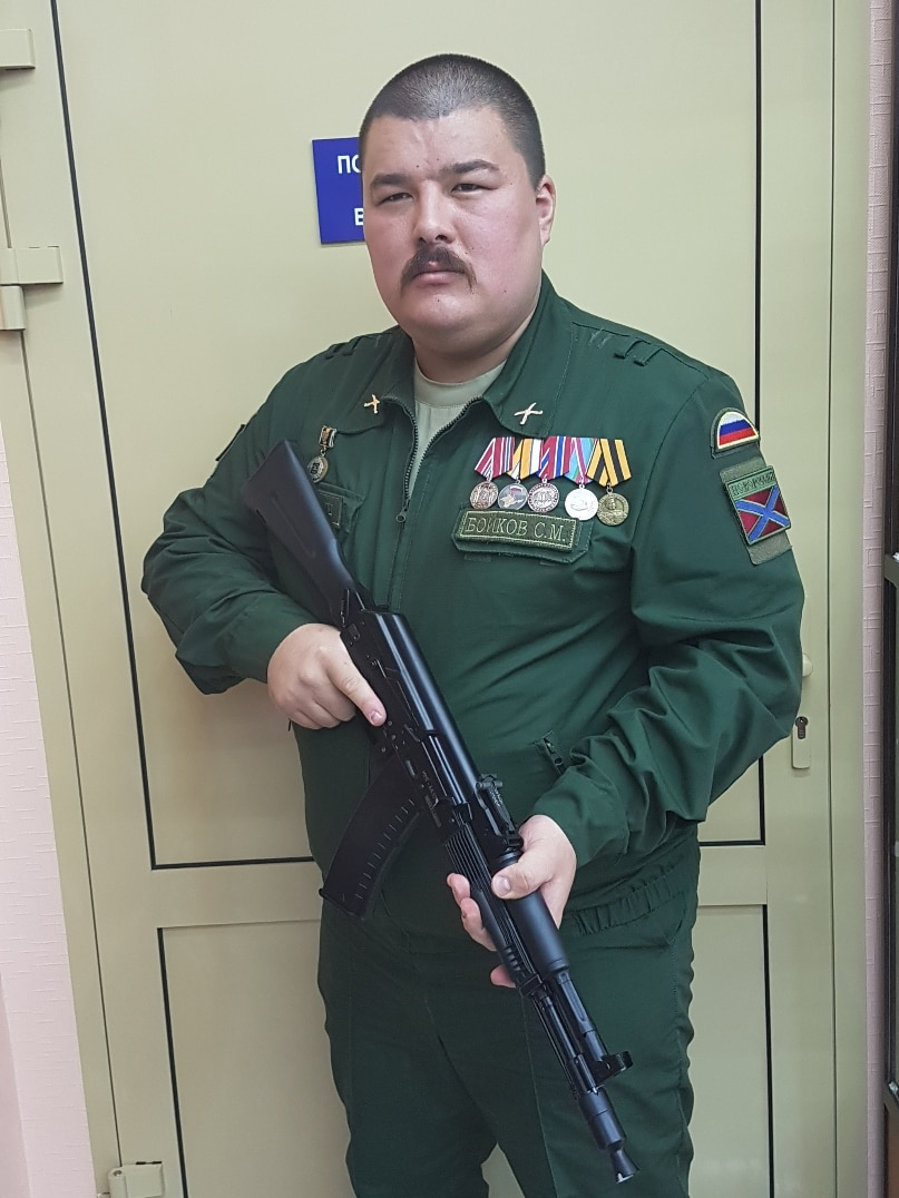 Man with shaved head and moustache wears green military outfit, holding machine gun, standing in front of door.