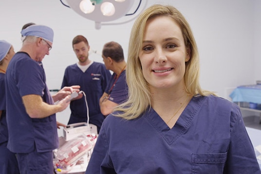 Heart surgeon Nikki Stamp stands in a operating room.