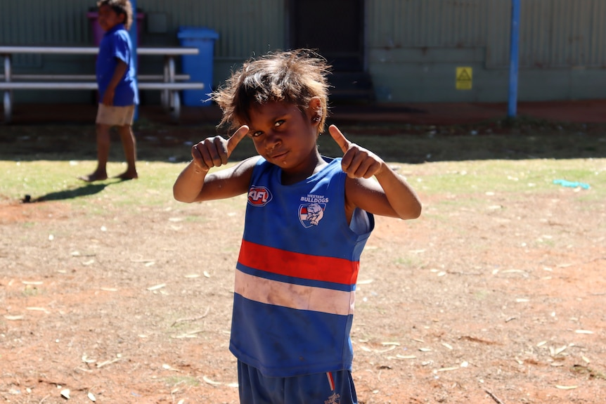 A young Aboriginal boy giving a thumbs up ... he is proudly wearing a sleeveless Western Bulldogs AFL top