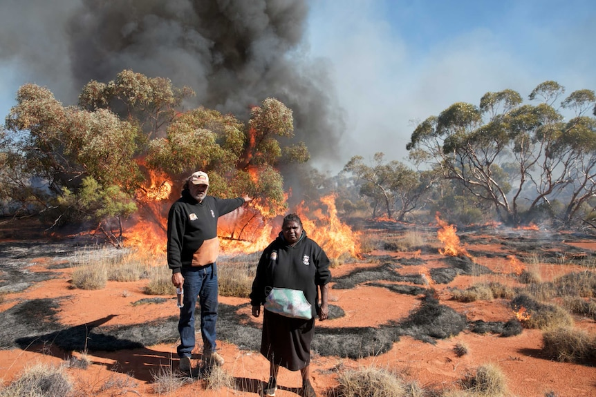 Two Indigenous people stand in the foreground as fire burns in scrub behind them.
