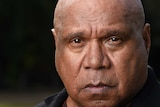 Indigenous musician Archie Roach stares into the camera lens as his portrait is taken.