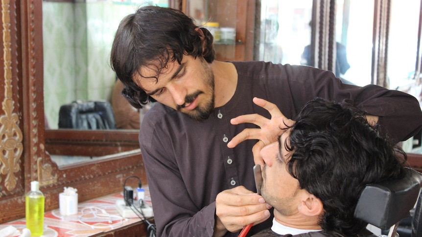 A barber wearing traditional Afghan attire cuts a man's beard in his shop