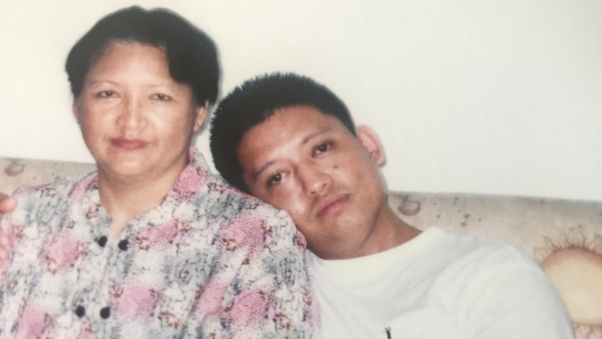 A woman in a floral top sitting next to her son, with his head leaning on her shoulder.