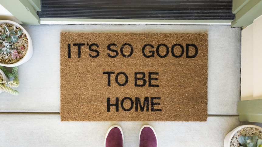 """A person stands in front of a welcome mat that says """"it's so good to be home""""."""