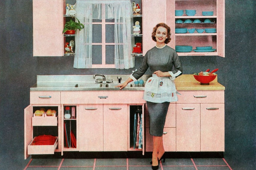 A grainy, old-looking coloured image of a woman in 1950s-style dress and apron, standing smiling near a sink in a tidy kitchen.