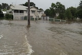 Floodwaters course down a street in Roma