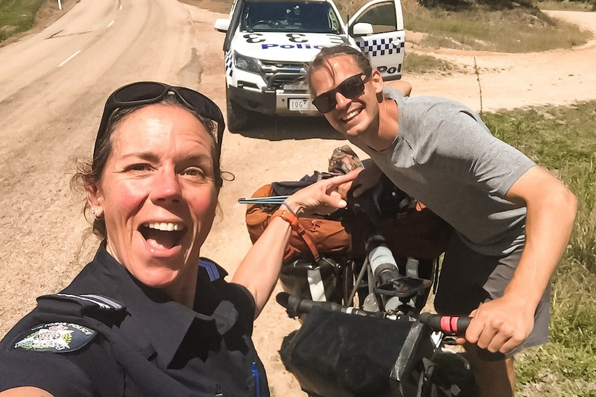 A surprised looking female police officer points at a smiling young man who is holding a bike