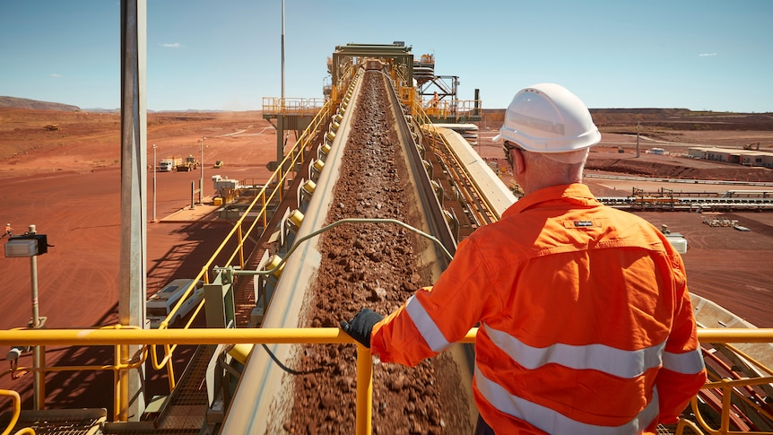 Man in high vis and hard hard looks over conveyor belt carrying iron ore at the South Flank mine.