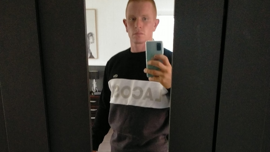 Jake Opacic takes a selfie. He has a full leg tatoo, ginger hair and wears shorts.