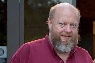 An older, bald man with a large red and white beard, wearing a dark red shirt.