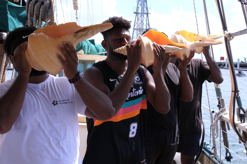 Four men blow through large conch looking shells