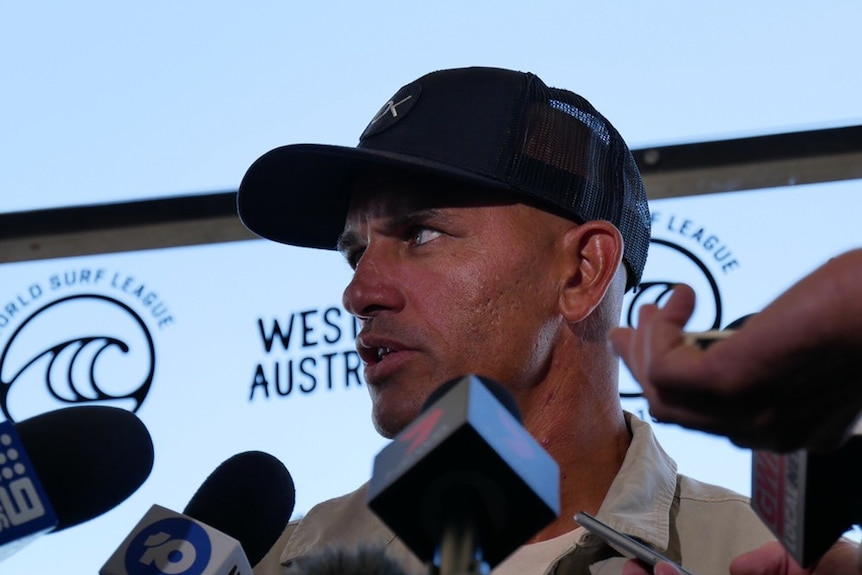 A low angle shot of a man with a hat on who is being questioned by the media.