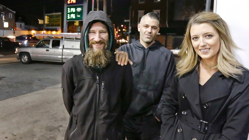 Close up shot of Johnny Bobbitt Jr., left, with a big smile, with Kate McClure, right, and her boyfriend M'Amico in the centre.