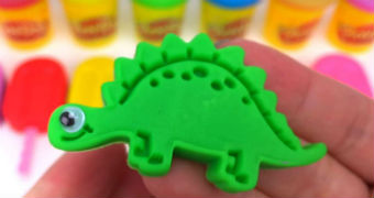 A pair of hands holds a green plasticine dinosaur.
