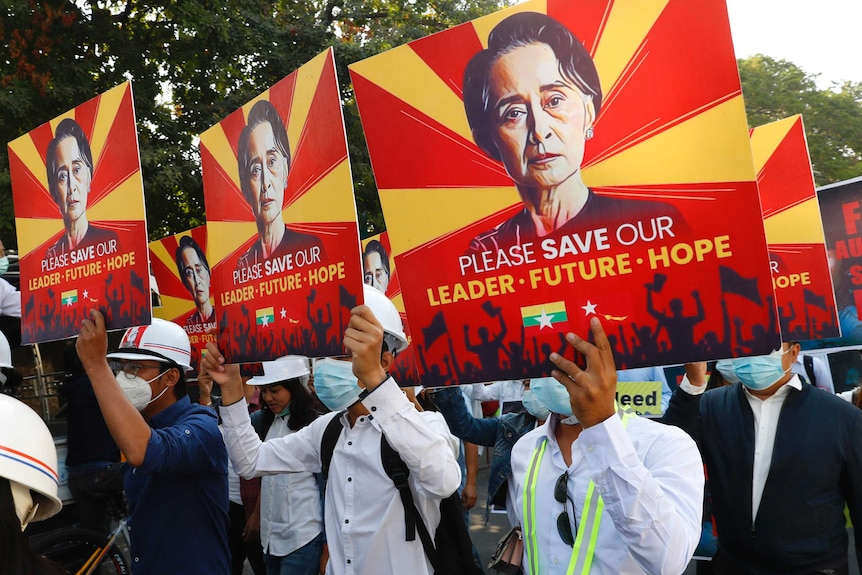 Anti-coup protesters in Myanmar are seen holding up signs showing Aung San Suu Kyi.