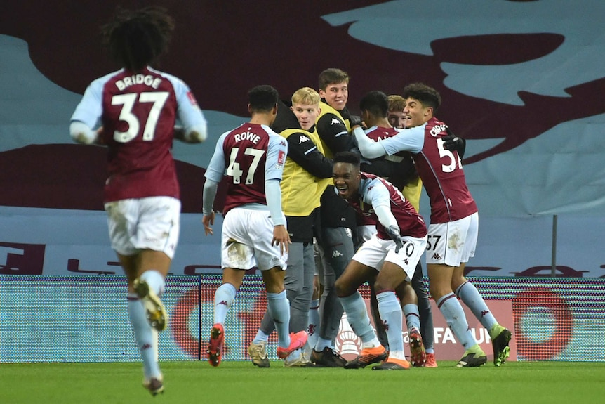 Players wearing claret and blue jerseys celebrate on a pitch.