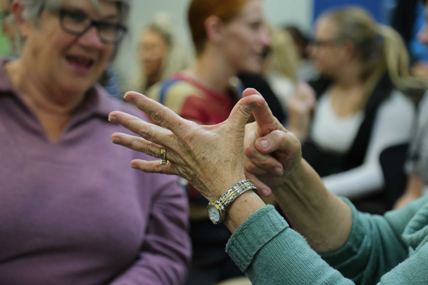 A close up image of a hand using sign language. Ausnew Home Care, NDIS registered provider, My Aged Care