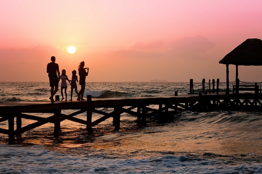 A family stands on a wharf at sunset.