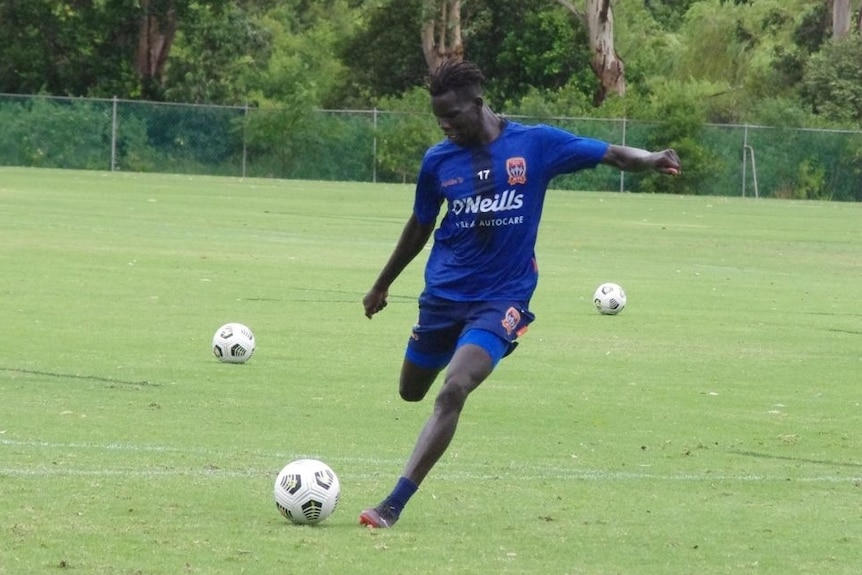 An African man in blue sports top and shorts prepares to kick a soccer ball while practising on a  green sports field.