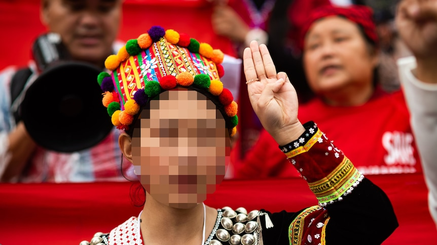 A woman in colourful traditional Kachin dress gives a three-finger salute. Her face is blurred.