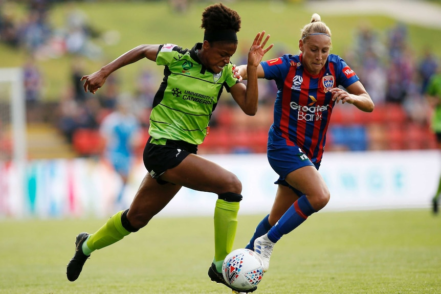 A W-League attacker runs with the ball down the wing as a defender tries to cut in on her.