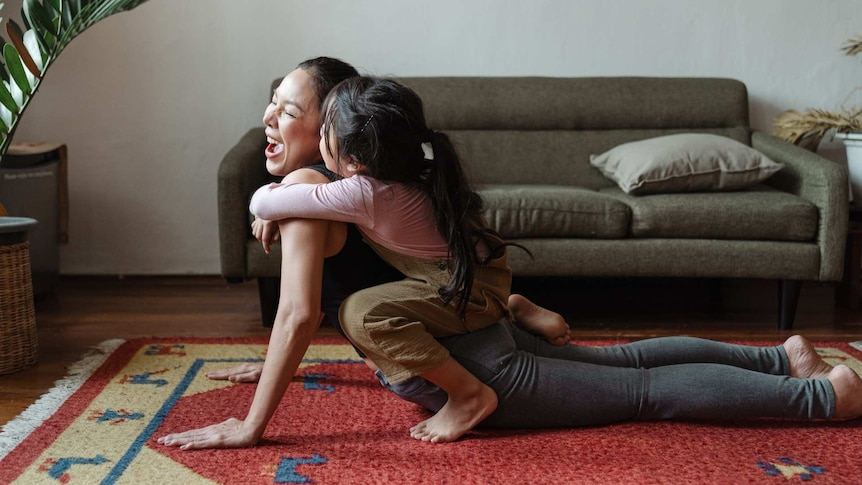 A woman doing yoga in a loungeroom with a young child climbing on her.