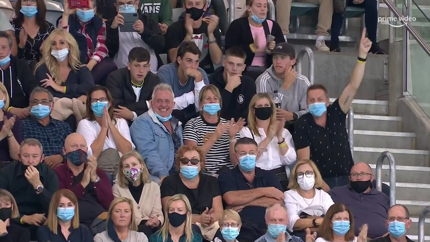 Four young men not wearing face masks while sitting in crowd of people all wearing masks.