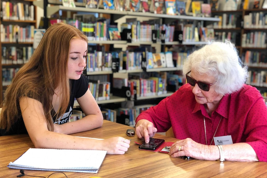 A teenage girl sits with elderly woman Ruth Holmes and teaches her how to use her mobile phone.