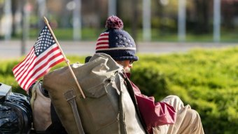 A homeless man with a US flag attached to his backpack.