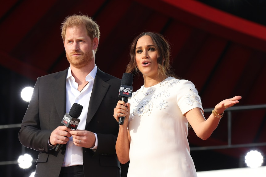 prince harry and meghan markle on stage at Global Citizen Live as Meghan speaks into a microphone