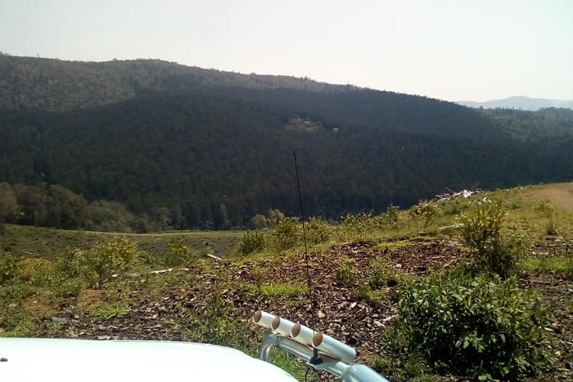 The bonnet of a four-wheel-drive, overlooking scrubland with mountains in the background.