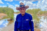 An elderly Indigenous man in a dark shirt and a hat, standing in front of a waterway fringed with trees.