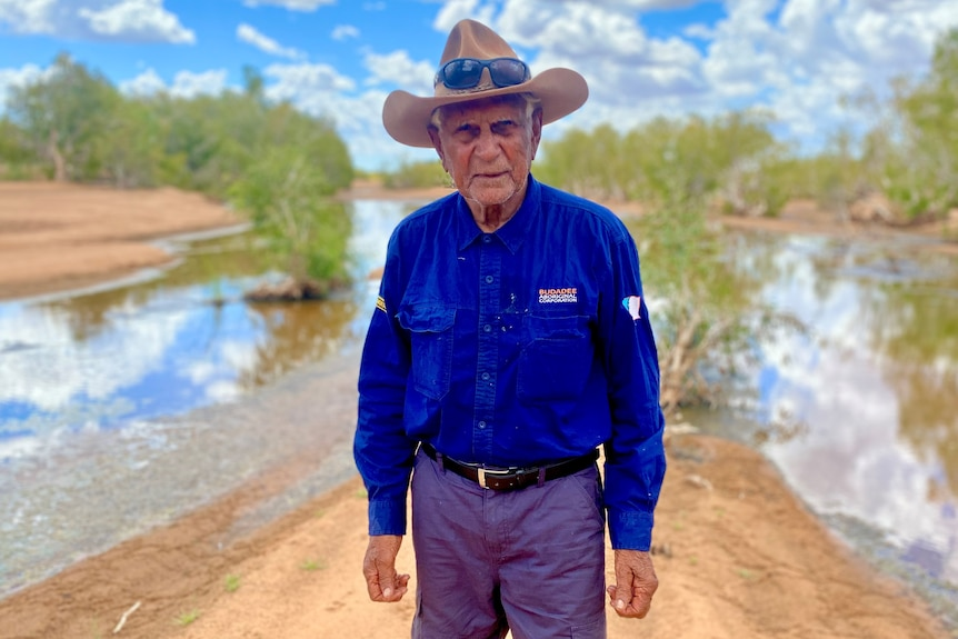 Stephen Stewart wears long blue shirt and hat with water and trees in the background.