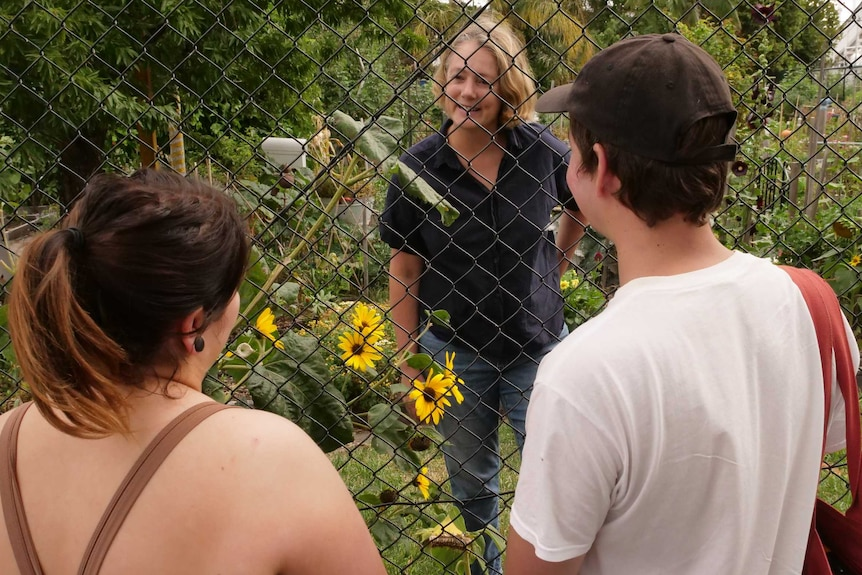 A woman looks through a fence and talks to a man and woman on the other side.
