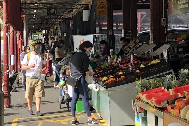 People wearing masks shopping for fruit and vegetables.