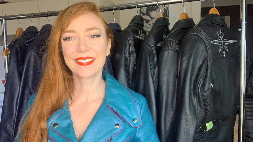 A woman with long red hair, wearing a bright blue leather jacket, stands in front of a rail of jackets.