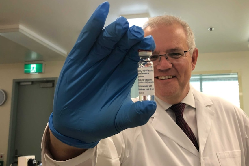 A man with grey hair and glasses holds up a vial of the AstraZeneca vaccine while wearing a white labcoat and blue gloves