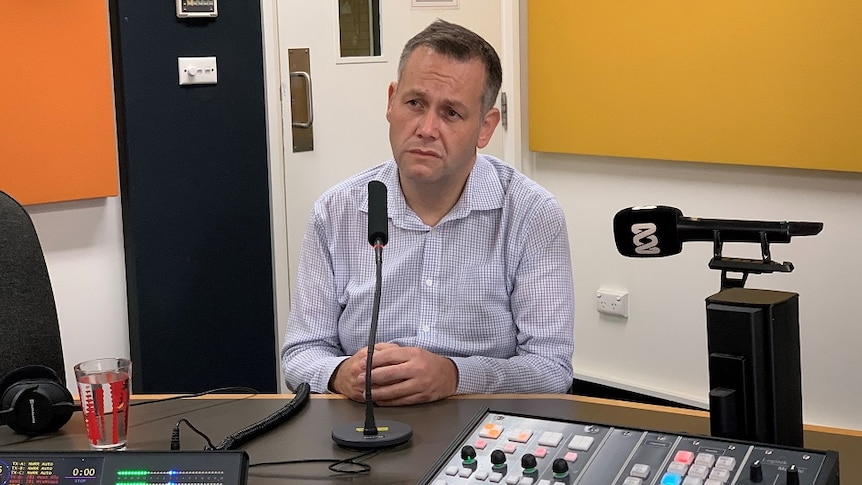Man sits looking unhappy in a radio studio
