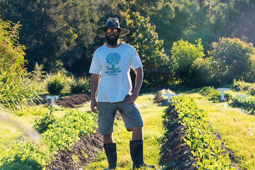 A man wearing gumboots and a broad-brimmed hat stands among rows of produce in a market garden.