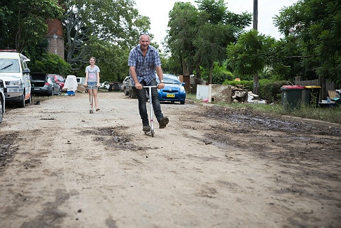A man rides his scooter down a dirty street in Murwillumbah
